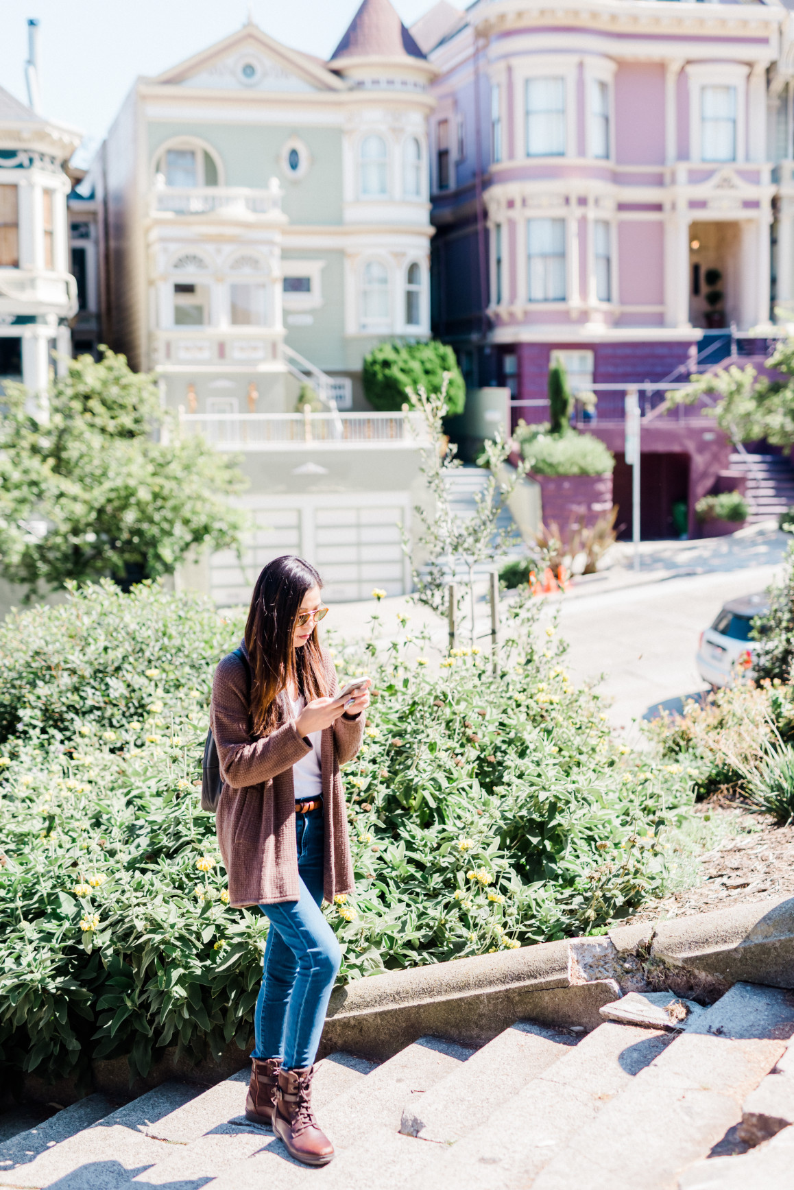 Photo of a person on their phone in front of private homes in SF